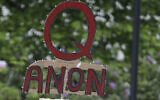 A person carries a sign supporting QAnon at a protest rally in Olympia, Washington, May 14, 2020. (Ted S. Warren/AP)