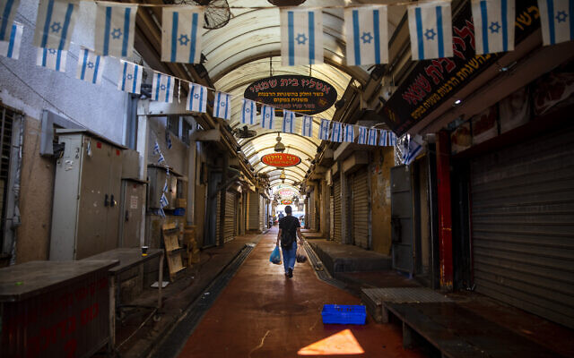 A man walks through a closed market amid a nationwide coronavirus lockdown, in Tel Aviv, September 18, 2020. (AP Photo/Oded Balilty)