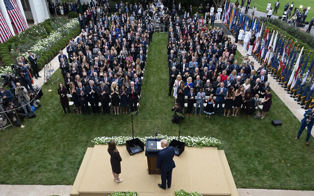 US President Donald Trump, center, stands with Judge Amy Coney Barrett as they arrive for a news conference to announce Barrett as his nominee to the Supreme Court, in the Rose Garden at the White House in Washington, Sept. 26, 2020. (AP Photo/Alex Brandon)