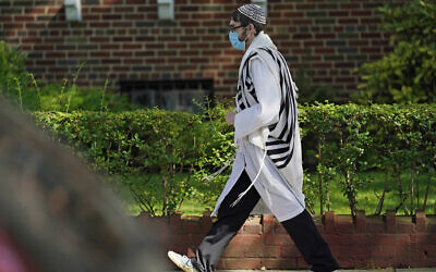 An Orthodox Jewish man walks through the Midwood neighborhood of Brooklyn on Yom Kippur, Sept. 28, 2020. (AP Photo/Kathy Willens)