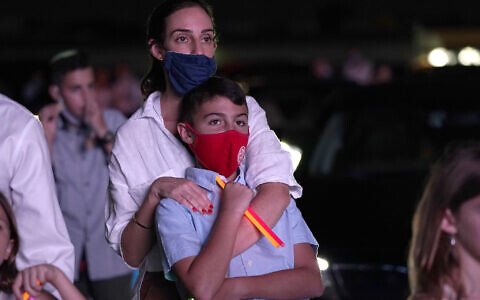 Illustrative: A woman stands with her son during a Yom Kippur service hosted by the Aventura Turnberry Jewish Center, during the coronavirus pandemic, Monday, Sept. 28, 2020, at the Dezerland Park drive-in theatre in North Miami, Fla. (AP Photo/Lynne Sladky)