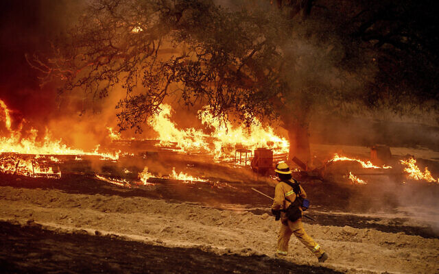 A US firefighter passes flames while battling the Glass Fire in a Calistoga, California, vineyard October 1, 2020. (AP Photo/Noah Berger)