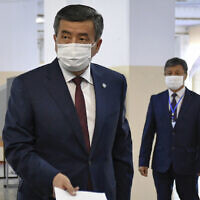 Kyrgyzstan's President Sooronbai Jeenbekov wearing a face mask casts his ballot paper during parliamentary elections in Bishkek, Kyrgyzstan, Oct. 4, 2020. (AP Photo/Vladimir Voronin)