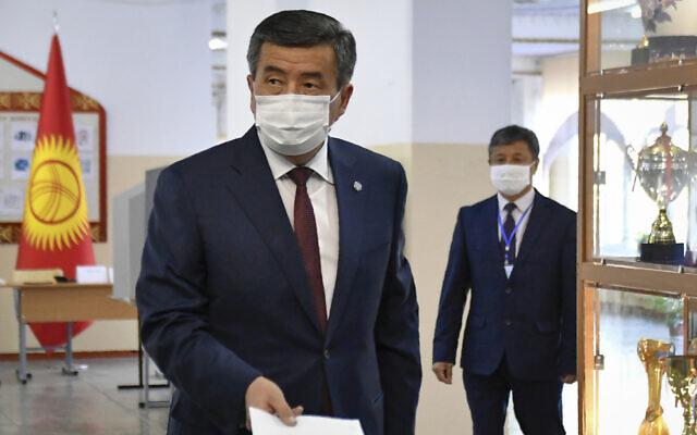 Kyrgyzstan's President Sooronbai Jeenbekov wearing a face mask casts his ballot paper during parliamentary elections in Bishkek, Kyrgyzstan, Oct. 4, 2020. (AP Photo/Vladimir Voronin)