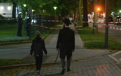 In this Oct. 4, 2020 photo a man and a boy walk towards the cordoned-off area in front of a synagogue in Hamburg, Germany that was the scene of an attack (Jonas Walzberg/dpa via AP)