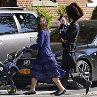 In this Oct. 4, 2020, photo, an Orthodox Jewish family crosses a street during the Jewish holiday of Sukkot in the Borough Park neighborhood in the Brooklyn borough of New York. Amid a new surge of COVID-19 in New York's Orthodox Jewish communities, many residents are reviving health measures that some had abandoned over the summer – social distancing, wearing masks. For many, there's also a return of anger: They feel the city is singling them out for criticism that other groups avoid. (AP Photo/Kathy Willens)