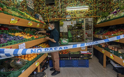 A no trespassing sign is used to keep social distance guidelines at a vegetable shop in Madrid, Spain, Oct. 6, 2020 (AP Photo/Bernat Armangue)