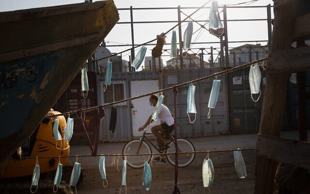 A man wearing face mask rides his bicycle next to boats with face masks hanging on them during a nationwide lockdown to curb the spread of the coronavirus, at Jaffa port near Tel Aviv, October 7, 2020. (Oded Balilty/AP)