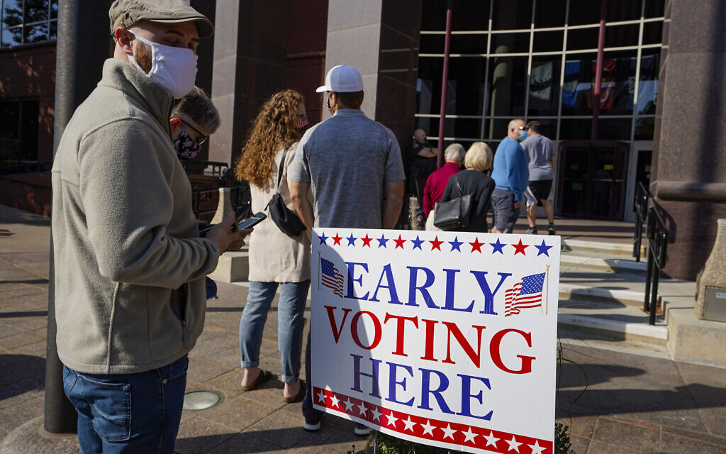 Voters wait in line at the Judicial Center in Noblesville, Indiana, Octobe 7, 2020, to cast their ballot on the second day of the state's early voting. (AP Photo/Michael Conroy)