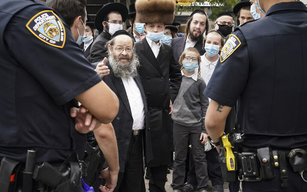 Members of the ultra-Orthodox community speak with NYPD officers on a street corner on October 7, 2020, in the Borough Park neighborhood of the Brooklyn borough of New York. (AP/John Minchillo)