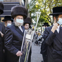 Members of the ultra-Orthodox community gather to listen in on an interview with a journalist, October 7, 2020, in the Borough Park neighborhood of the Brooklyn borough of New York. (AP Photo/John Minchillo)