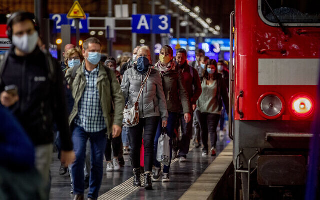 Passengers wear face masks as they leave a train in the central train station in Frankfurt, Germany, October 8, 2020. (AP Photo/Michael Probst)