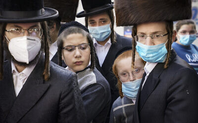 Illustrative: Members of the Jewish Orthodox community gather around a journalist as he conducts an interview on a street corner, October 7, 2020, in the Borough Park neighborhood of the Brooklyn borough of New York.  (AP Photo/John Minchillo)
