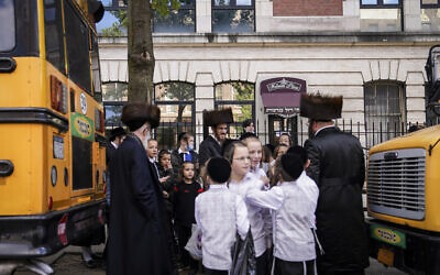 Members of the Orthodox Jewish community wait for school buses to collect them in the Borough Park neighborhood of the Brooklyn borough of New York, October 8, 2020. (AP Photo/John Minchillo)