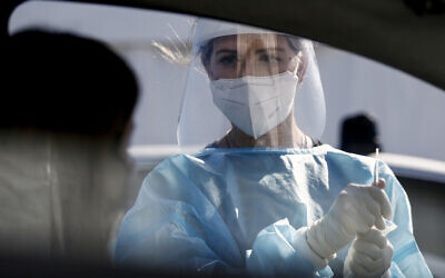 A medical staffer performs tests for the coronavirus at a drive-through at Rome's Leonardo Da Vinci airport, Friday, Oct. 9, 2020. Italy's new confirmed caseload Friday passed 5,372, the highest levels since March. (Cecilia Fabiano/LaPresse via AP)