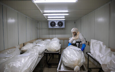 A worker from 'Hevra Kadisha,' Israel's official Jewish burial society, prepares bodies at a special morgue for COVID-19 victims in Holon, near Tel Aviv, October 12, 2020. (AP Photo/Oded Balilty)
