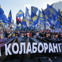 "People carry flags of right-wing party Svoboda and a banner reading ""Fight to collaborators!"" during a rally marking Defender of Ukraine Day in centre Kyiv, Ukraine, October 14, 2020. (AP Photo/Efrem Lukatsky)"