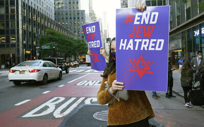 A young woman holds a sign toward oncoming traffic on Third Avenue outside the offices of New York Gov. Andrew Cuomo, Thursday, Oct. 15, 2020, in New York.  (AP Photo/Kathy Willens)