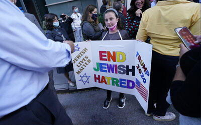 A young girl holds a poster she made as she joined protesters outside the offices of New York Gov. Andrew Cuomo, Thursday, Oct. 15, 2020, in New York.  (AP Photo/Kathy Willens)