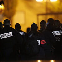 French police officers gather outside a high school after a history teacher who opened a discussion with students on caricatures of Islam's Prophet Muhammad was beheaded in Conflans-Saint-Honorine, north of Paris, October 16, 2020. (AP Photo/Michel Euler)