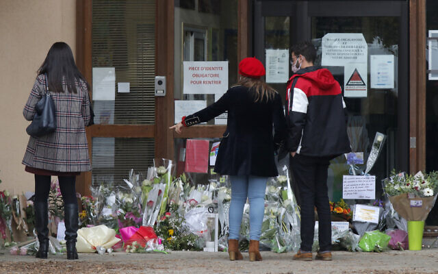 People stand by flowers laid outside the school where a slain history teacher was working, Oct. 17, 2020 in Conflans-Sainte-Honorine, northwest of Paris (AP Photo/Michel Euler)