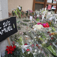 "A poster reading ""I am Samuel"" and flowers lay outside the school where slain history teacher Samuel Paty was working, Saturday, Oct. 17, 2020 in Conflans-Sainte-Honorine, northwest of Paris. (AP Photo/Michel Euler)"