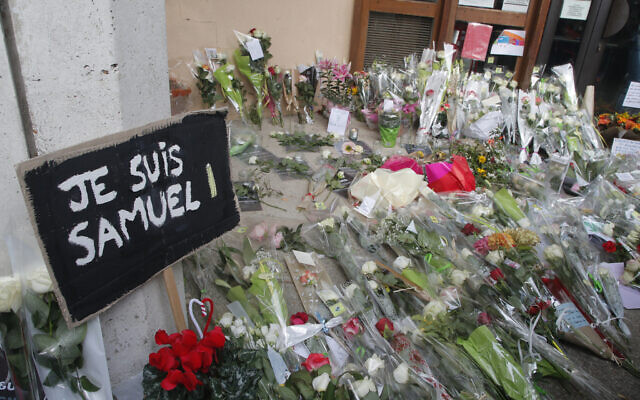 """A poster reading """"I am Samuel"""" and flowers outside the school where slain history teacher Samuel Paty worked, on October 17, 2020, in Conflans-Sainte-Honorine, northwest of Paris. (AP/Michel Euler)"""