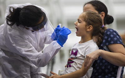 A young girl is tested for the coronavirus by a healthcare worker at a COVID-19 testing center set up at a basketball court, in Ramat Gan, Oct 20, 2020. (AP Photo/Oded Balilty)