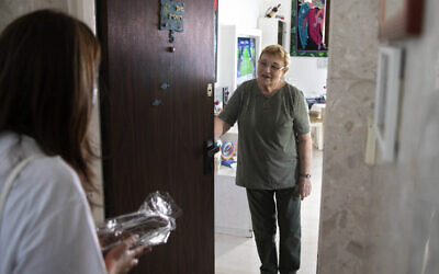 Israeli volunteer Sharon Yaron, left, brings a cake to 85-year-old Holocaust survivor Sara Weinsten during a visit to her house in Yavne, Israel, October 8, 2020. (AP Photo/Sebastian Scheiner)
