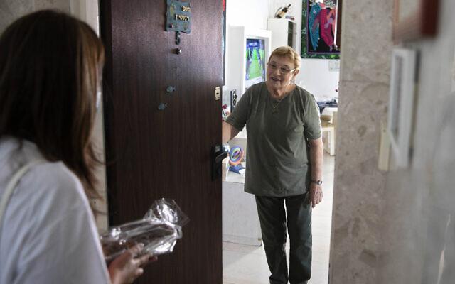 Israeli volunteer Sharon Yaron, left, brings a cake to 85-year-old Holocaust survivor Sara Weinsten during a visit to her house in Yavne, Israel, October 8, 2020. (AP Photo/Sebastian Scheiner)