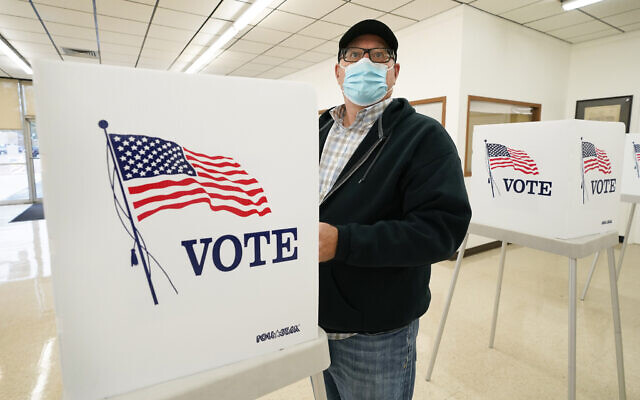 A man fills out his ballot during early voting for the US presidential election, October 20, 2020, in Adel, Iowa. (AP Photo/Charlie Neibergall)