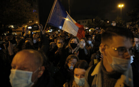 People attend a memorial march in homage to the history teacher who was beheaded last week, Tuesday, Oct.20, 2020 in Conflans-Sainte-Honorine, northwest of Paris. Samuel Paty was beheaded on Friday by an 18-year-old Moscow-born Chechen refugee, who was later shot dead by police. Police officials said Paty had discussed caricatures of Islam's Prophet Muhammad with his class, leading to threats. (AP Photo/Lewis Joly)