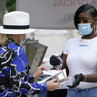 A woman drops off a vote-by-mail ballot with an election worker, right, at an official ballot drop box outside of an early voting site, October 20, 2020, in Miami Beach, Florida (AP Photo/Lynne Sladky)