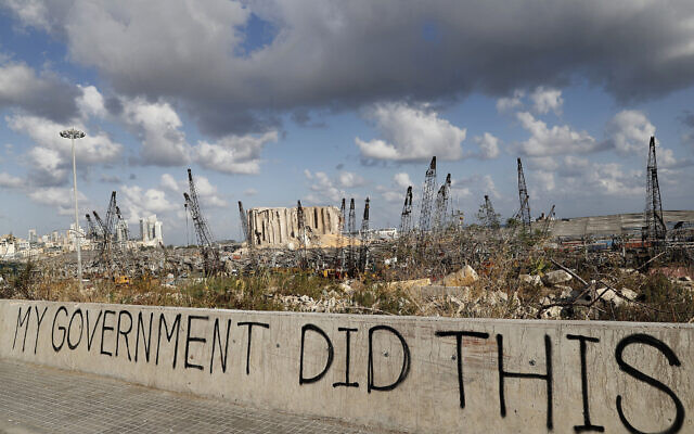 Political graffiti is visible in front of the scene of the August 4 explosion that hit the seaport of Beirut, Lebanon, August 9, 2020. (AP/Hussein Malla)