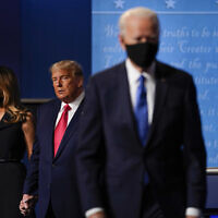 First lady Melania Trump, left, andUS President Donald Trump, center, remain on stage as Democratic presidential candidate former Vice President Joe Biden, right, walk away at the conclusion of the second and final presidential debate Thursday, Oct. 22, 2020, at Belmont University in Nashville, Tenn. (AP Photo/Julio Cortez)