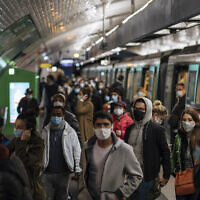 Commuters wearing face masks walk on the platform, of a Paris subway, Oct.25, 2020 (AP Photo/Lewis Joly)
