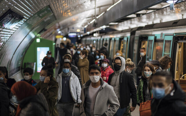 Commuters wearing face masks walk on the platform, of a Paris subway, Oct.25, 2020 (AP Photo/Lewis Joly)