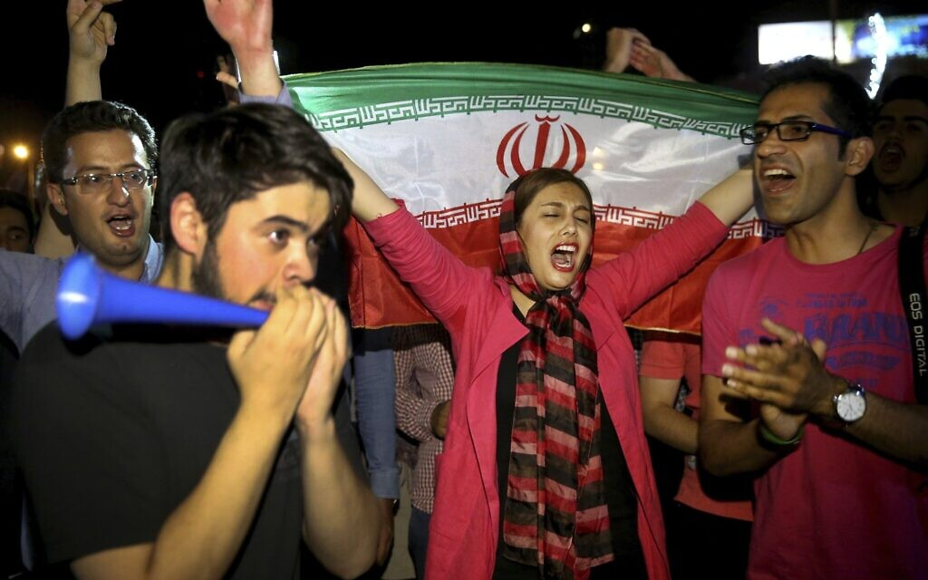 In this July 14, 2015, photo, an Iranian woman holds up a national flag as people celebrate a landmark nuclear deal, in Tehran, Iran. (AP Photo/Ebrahim Noroozi)