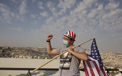 A supporter of US President Donald Trump wears a hat in the colors of the American flag at a rally for his re-election, at a promenade overlooking Jerusalem, October 27, 2020. (AP/Maya Alleruzzo)
