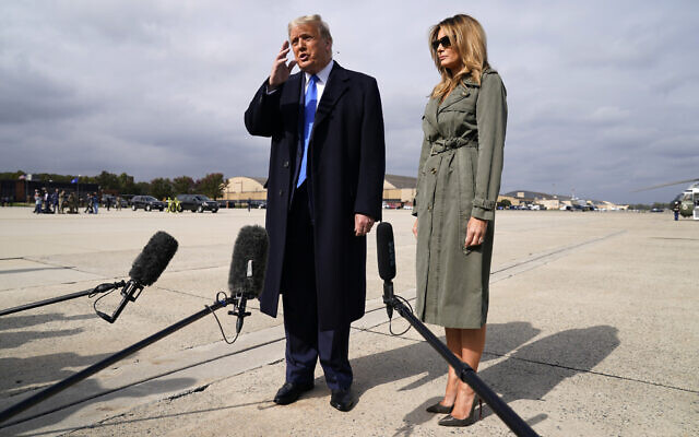 US President Donald Trump talks to reporters as first lady Melania Trump listens before boarding Air Force One for a day of campaign rallies in Michigan, Wisconsin, and Nebraska, October 27, 2020, at Andrews Air Force Base, Maryland. (AP Photo/Evan Vucci)