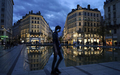 A man wearing a mask walks in the street in the center of Lyon, central France, Wednesday, Oct. 28, 2020. France is bracing for a potential new lockdown as the president prepares a televised address Wednesday aimed at stopping a fast-rising tide of virus patients filling French hospitals and a growing daily death toll.  (AP Photo/Laurent Cipriani)
