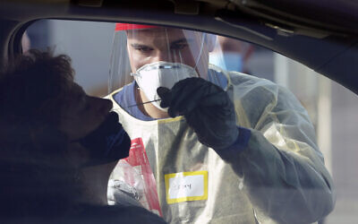 Cody Tupen, a firefighter with the Puget Sound Regional Fire Authority, performs a deep nasal nose-swab COVID-19 test on Nancy Backus, left, the mayor of Auburn, Washington, at a King County COVID-19 testing site in Auburn, south of Seattle, October 28, 2020. (AP Photo/Ted S. Warren)