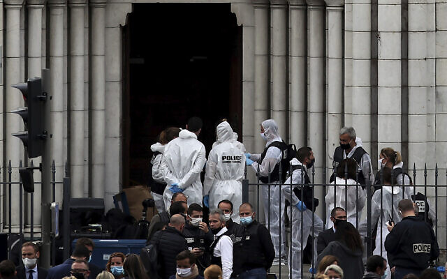 French policemen and forensic officers work on the scene of the knife attack in front of Notre Dame church, in Nice, France, October 29, 2020. An attacker armed with a knife killed three people at a church in the Mediterranean city of Nice, the third attack in two months in France. (AP Photo/Daniel Cole)