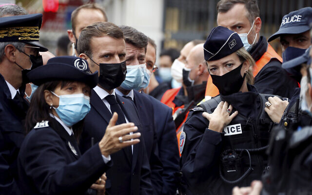 French President Emmanuel Macron, second left, and Nice mayor Christian Estrosi , third left, meet police officers after a knife attack at Notre Dame church in Nice, southern France, October 29, 2020. (Eric Gaillard/Pool via AP)