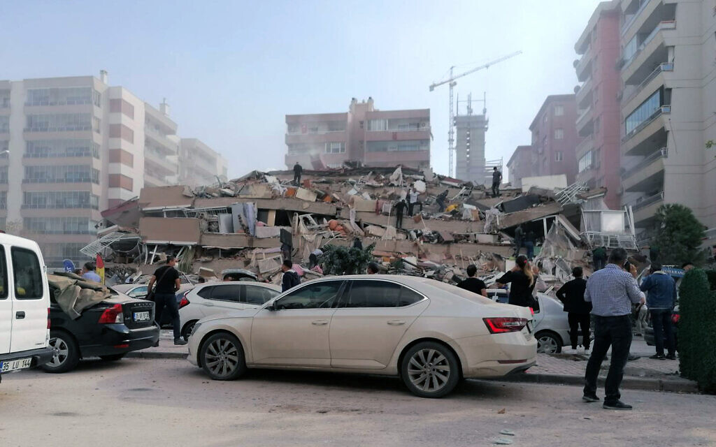 People work on a collapsed building, in Izmir, Turkey, Oct. 30, 2020, after a strong earthquake in the Aegean Sea has shaken Turkey and Greece (DHA via AP)