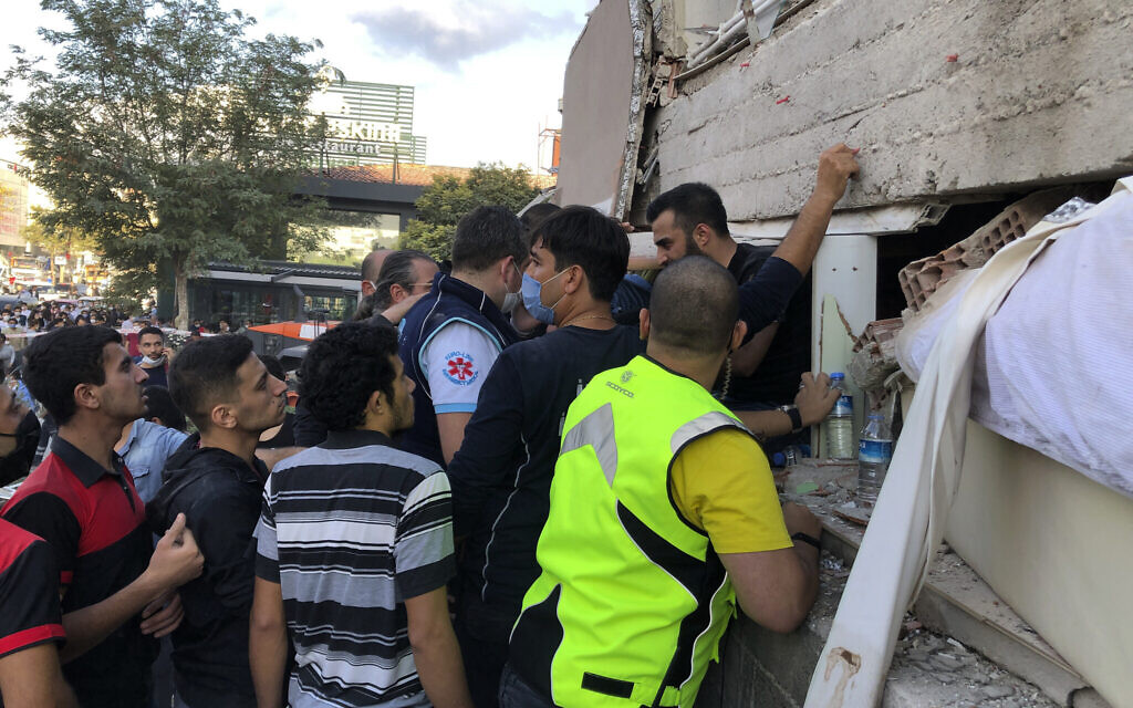 Rescue workers and local people try to reach residents trapped in the debris of a collapsed building, in Izmir, Turkey, Friday, Oct. 30, 2020, after a strong earthquake in the Aegean Sea has shaken Turkey and Greece. (AP Photo/Ismail Gokmen)