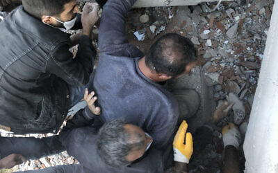 Rescue workers and local people try to reach residents trapped in the debris of a collapsed building, in Izmir, Turkey, Friday, Oct. 30, 2020, after a strong earthquake in the Aegean Sea has shaken Turkey and Greece. T(AP Photo/Ismail Gokmen)