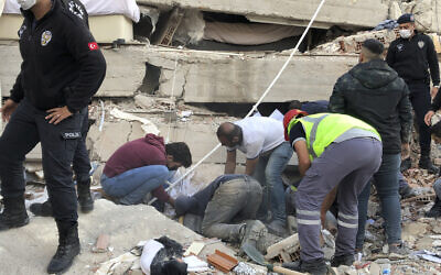 Rescue workers and local people try to save residents trapped in the debris of a collapsed building, in Izmir, Turkey, Friday, Oct. 30, 2020, after a strong earthquake in the Aegean Sea has shaken Turkey and Greece.(AP Photo/Ismail Gokmen)