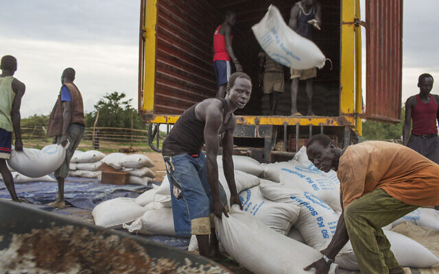 Workers offload sacks of cereals from the United Nations World Food Program (WFP) off a truck in Minkaman, South Sudan, June 26, 2014 (AP Photo/Matthew Abbott)