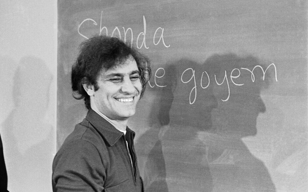 Abbie Hoffman smiles at the blackboard during a news conference, February 5, 1970 in Chicago. He's among the Chicago 7 on trial for conspiracy to cause riots at the time of the Democratic National Convention. (AP Photo/Jim Palmer)